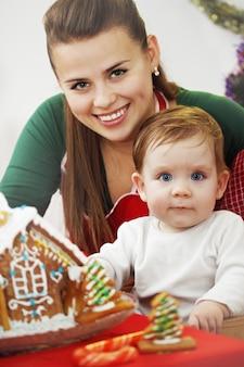 Mãe com filho fazendo uma casa de pão de gengibre