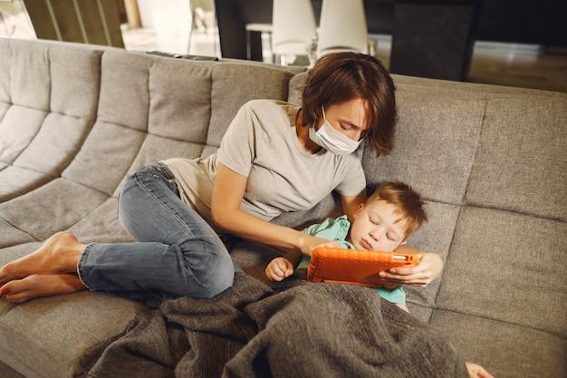 Mãe com filho menor sentado em casa em quarentena