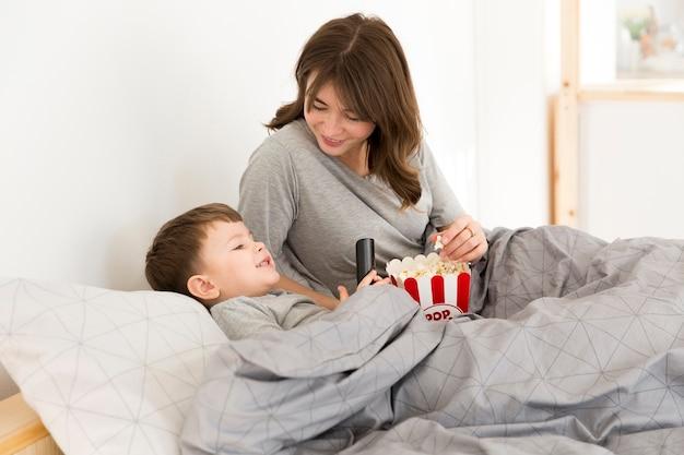 Mãe com filho na cama comendo pipoca