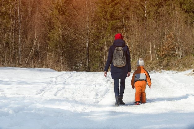 Mãe com filho pequeno andando pela estrada coberta de neve na floresta de coníferas.