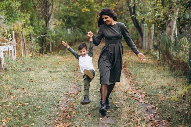Mãe com filho pequeno em um parque de outono