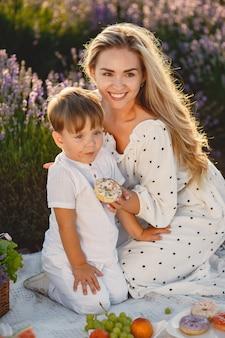 Mãe com filho pequeno no campo de lavanda. mulher a um piquenique com o filho.