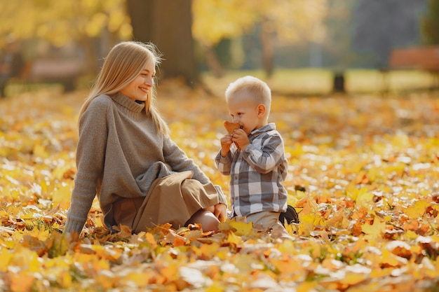 Mãe com filho pequeno, sentado em um campo de outono