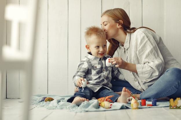 Mãe com filho se preparando para a páscoa em casa