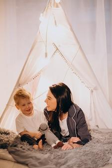 Mãe, com, filho sentando, em, cozy, barraca, com, luzes, casa, natal