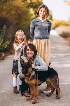 Mãe com filhos e cachorro em um parque de outono