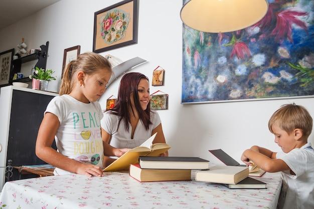 Mãe com filhos e livros