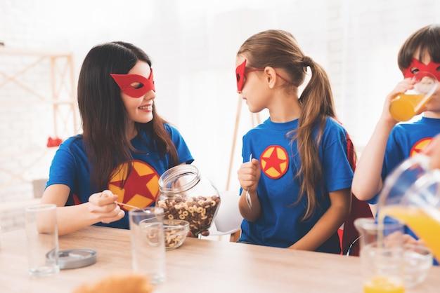 Mãe com filhos em ternos vermelhos e azuis de super-heróis.