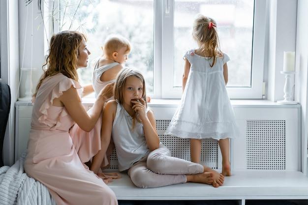Mãe com filhos em um ambiente caseiro. crianças pela janela