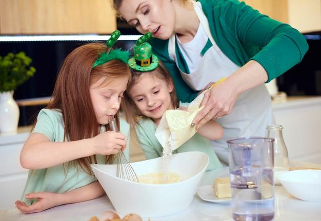 Mãe com filhos fazendo biscoitos