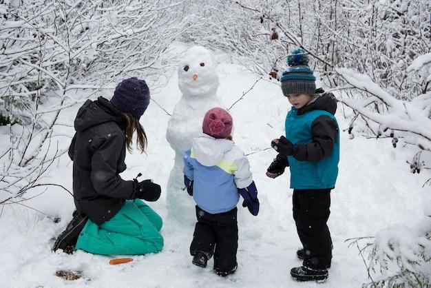 Mãe com filhos fazendo boneco de neve