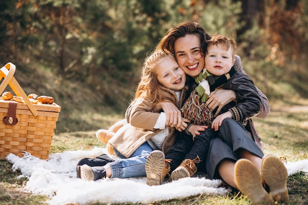 Mãe com filhos fazendo piquenique na floresta