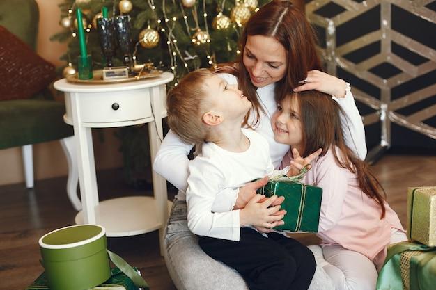 Mãe com filhos fofos perto da árvore de natal