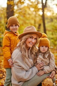 Mãe com filhos na natureza de outono, adorável adorável fêmea com casaco, curtindo o tempo com crianças pequenas na floresta de outono