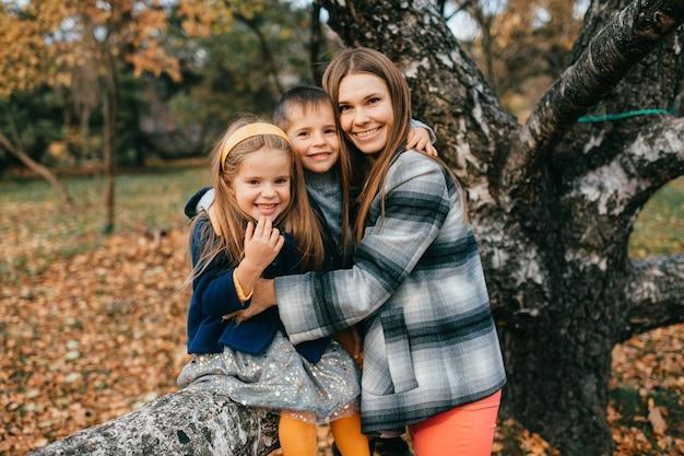 Mãe com filhos no parque outono