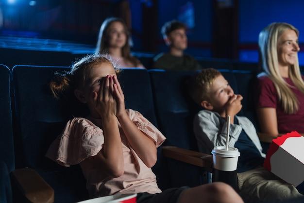 Mãe com filhos pequenos no cinema, assistindo filme.