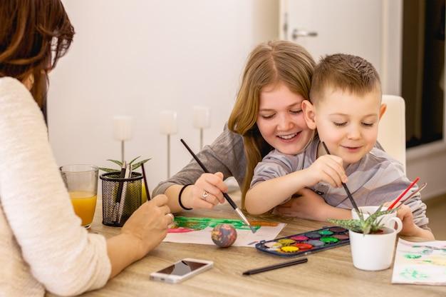 Mãe com filhos pintando e se divertindo
