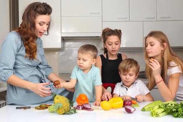 Mãe com filhos preparando legumes na cozinha