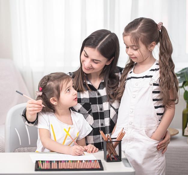 Mãe com filhos sentados à mesa e fazendo lição de casa. a criança aprende em casa. educação escolar em casa. espaço para texto.