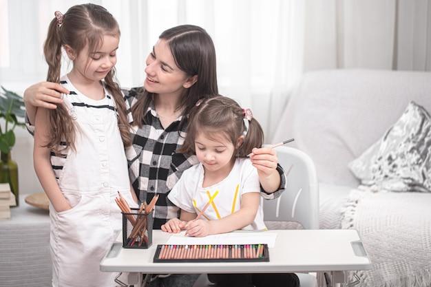 Mãe com filhos sentados à mesa e fazendo lição de casa.