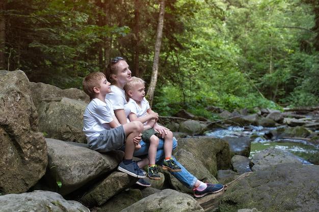 Mãe com filhos sentados em um rio de montanha e floresta selvagem. viaje com a família. ecoturismo