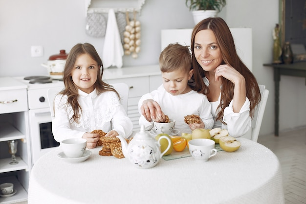 Mãe com filhos sentados em uma cozinha e fazer uma refeição