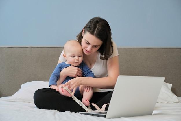 Mãe com fita de centímetro, medindo seu bebê sentado em casa