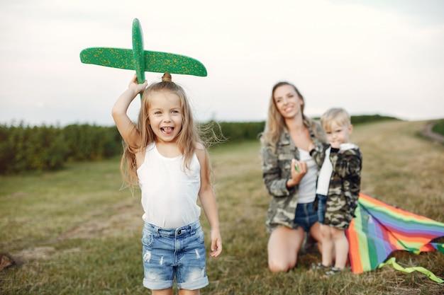 Mãe com giros filhinhos em um campo de verão