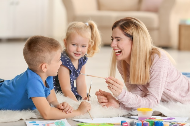 Mãe com lindos filhos pintando, dentro de casa