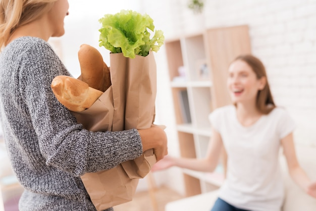 Mãe com maços de comida da loja em casa.