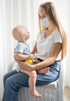 Mãe com máscara médica segurando a criança em casa durante a quarentena