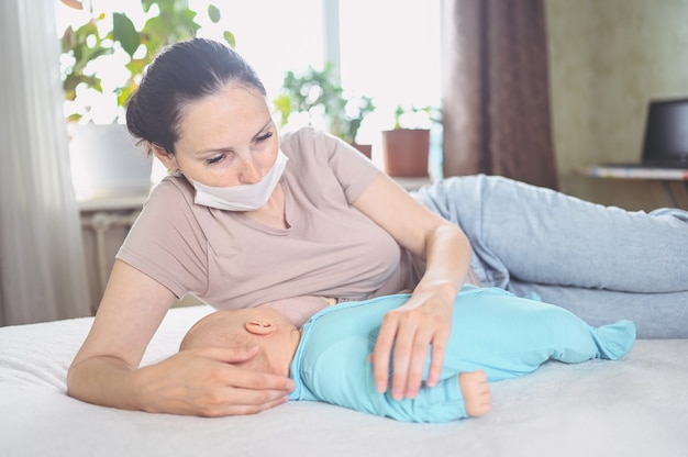 Mãe com máscara protetora com bebê recém-nascido em macacão amamenta com leite materno