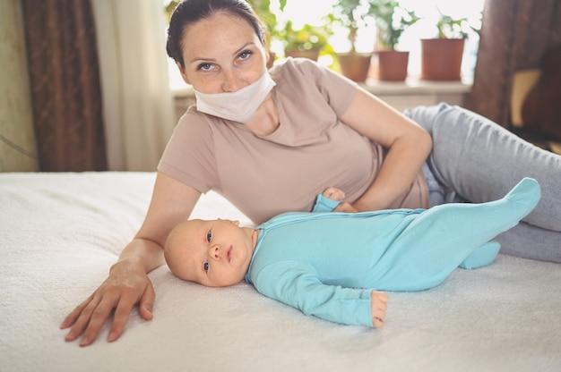 Mãe com máscara protetora com bebê recém-nascido em macacão azul abraçando-o deitado na cama