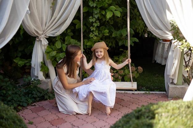 Mãe com menina brincando no ensolarado jardim florescendo