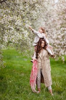Mãe com menina criança brincando no jardim primavera florescendo. mulher com filha abraçando e se divertindo ao ar livre. conceito de família feliz