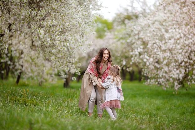 Mãe com menina criança brincando no jardim primavera florescendo. mulher com filha se divertindo ao ar livre.