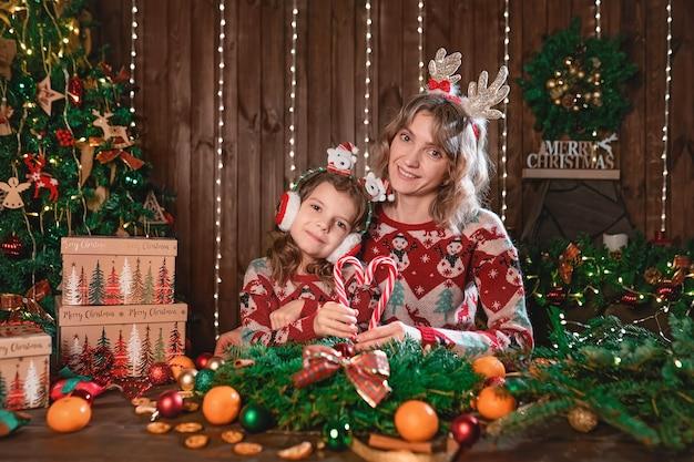 Mãe com menina criança perto de árvore de natal. feriados de ano novo.