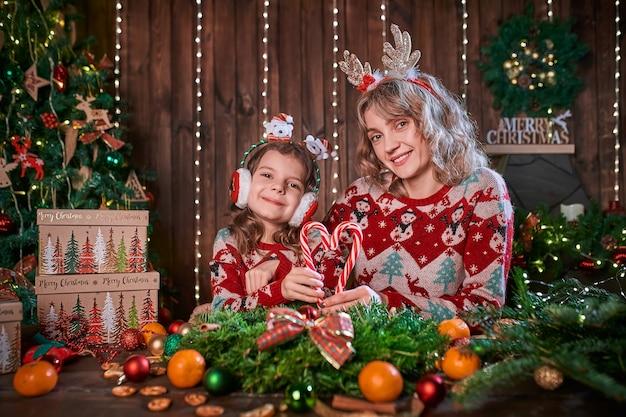 Mãe com menina criança perto de árvore de natal.