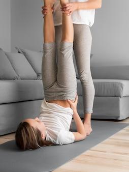Mãe com menina exercício fazendo pose de vela