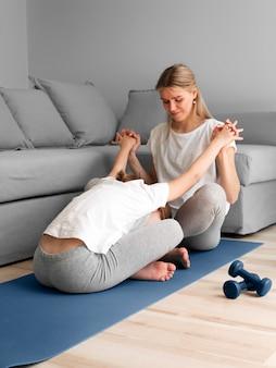 Mãe com menina exercitar em casa
