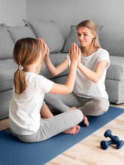 Mãe com menina exercitar na esteira
