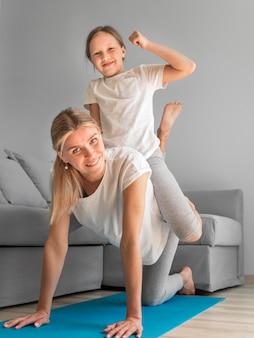 Mãe com menina nas costas exercício