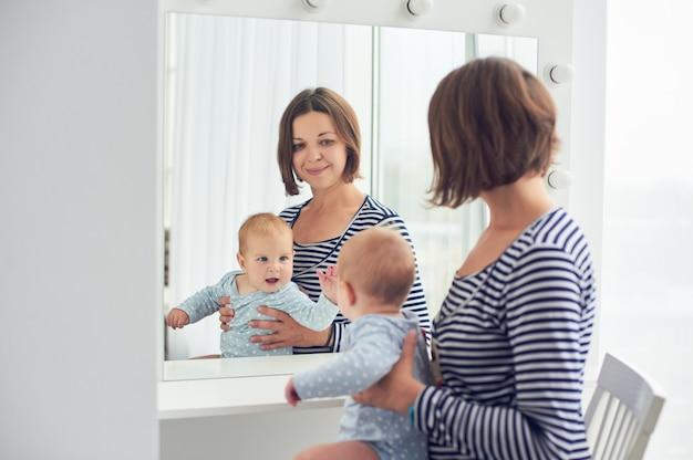 Mãe com o bebê de 8 meses se olha em um espelho em casa