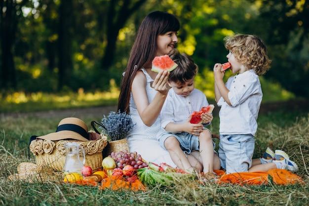 Mãe com os filhos fazendo piquenique no parque