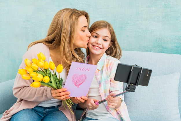Mãe, com, presentes, beijando, filha, levando, selfie