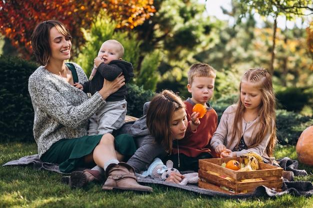 Mãe com quatro filhos fazendo piquenique no quintal