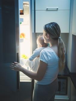 Mãe com seu bebê abrindo a geladeira tarde da noite