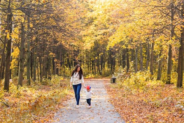 Mãe com seu bebê. mãe e filha em um parque de outono.