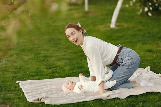 Mãe com seu bebê passar o tempo em um jardim de verão