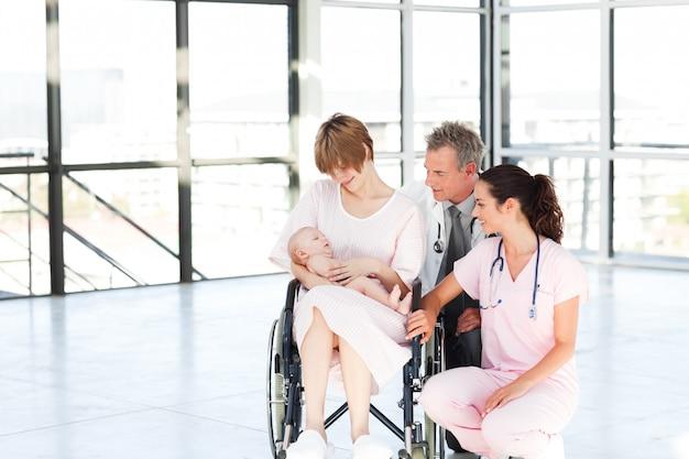 Mãe com seu bebê recém nascido e médicos com cópia-espaço